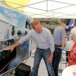 Bürgermeister Steffen Mues zeigt eine Bürgerin die Pläne zur Stufenanlage
