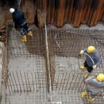 Bauarbeiter verteilen den Frischbeton für das Fundament der Ufermauer.