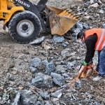 Foto: Bauarbeiter zerkleinern Geröll und Schutt am Uferbereich in Handarbeit.