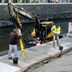 Foto: Ein Vermessungstechniker prüft die Lagegenauigkeit der neuen Uferplatten.