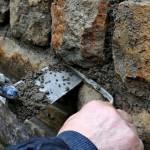 Foto: Echte Handarbeit - Stein um Stein wird der Mörtel an der Bruchsteinmauer mit der Kelle verfüllt.