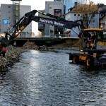 Foto: Ein Bagger glättet die neu angelegte Uferbefestigung.