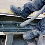 Im Hammerhütterweg gießen Bauarbeiter am Wegrand neue Gesimsbalken aus Beton, die später das neue Geländer tragen werden.